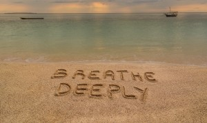 "Iere there is an inscription on the sand ""Breathe Deeeply""."